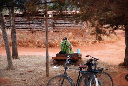 marginalization: A woman sitting on a street sells a drink, Pomerini, Tanzania, Africa - A woman sitting on a bench along a gravel road sells a drink
