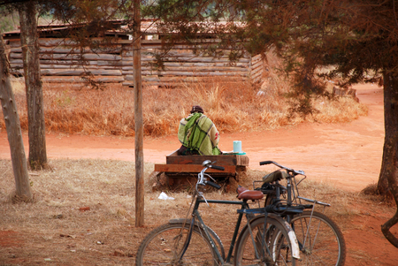 marginalization: A woman sitting on a bench along a gravel road sells a drink Stock Photo