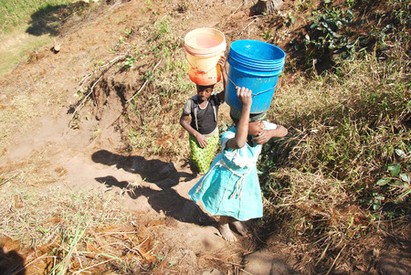 breathlessness: August 8, 2014, Mountain of Kilolo, Tanzania, Africa-Two unidentified girls as they climb the difficult ascent  from the river with in head two buckets full of water, a task that mostly only children perform Editorial