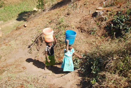 difficult task: August 8, 2014, Mountain of Kilolo, Tanzania, Africa-Two unidentified girls as they climb the difficult ascent  from the river with in head two buckets full of water, a task that mostly only children perform Editorial
