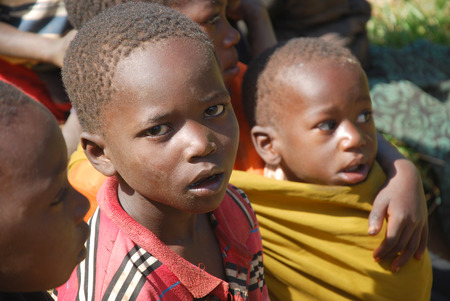 August 8, 2014, Mountain of Kilolo, Kilolo, Tanzania, Africa-A group of unidentified African children on the Mount of Kilolo gathered around the white volunteers of the international non-profit organization that brought food, medicines and clothes Redactioneel