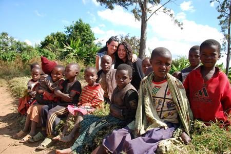 August 8, 2014, Mountain of Kilolo, Kilolo,Tanzania, Africa-A group of unidentified African children on the Mount of Kilolo gathered around the white volunteers of the international non-profit organization that brought food, medicines and clothes