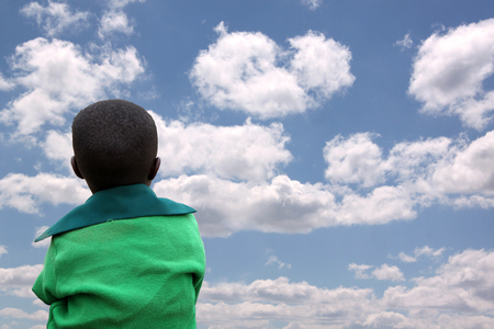 african solidarity: Go with the clouds - An African child with the eyes toward the clouds that go