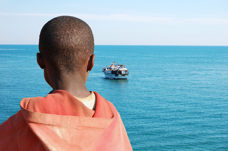 emigranti: Un bambino africano mentre guarda una chiatta con i suoi amici a bordo Archivio Fotografico