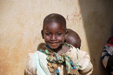 8 augustus 2015, Pomerini-Tanzania-Afrika-Two niet-geïdentificeerde Afrikaanse kinderen, meestal ouder zijn kinderen om kleinere verwaarloosd door de ouders vaak ziek of dood aan aids of tuberculose kijken Redactioneel