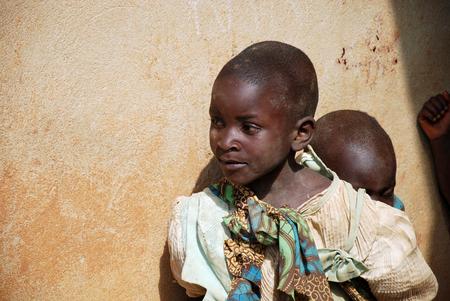 8 augustus 2015, Pomerini-Tanzania-Afrika-Twee niet-geïdentificeerde Afrikaanse kinderen, normaal zijn oudere kinderen om er kleiner uit te zien, verwaarloosd door ouders die vaak ziek of dood zijn door aids of tuberculose