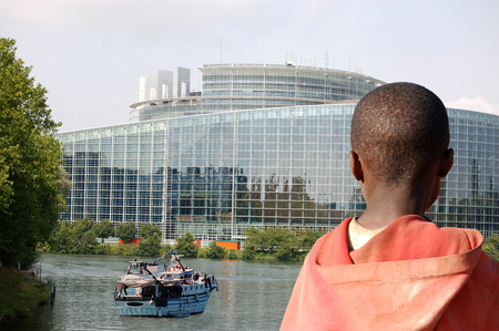 african solidarity: Here we are in Europe - An African child watches the arrival of a barge in Europe