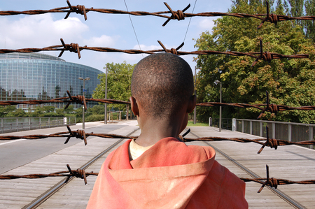 african solidarity: This is the Europe of Freedom? - An African child in front of a barbed wire fence Stock Photo