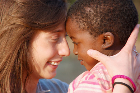 """March 28, 2016-Center """"Smile to Africa"""" in the Village Pomerini in Tanzania-Africa-An unidentified volunteer doctor embraces an unidentified African child, a little patients sick of AIDS, in a gesture of affection that expresses happiness for the success"""