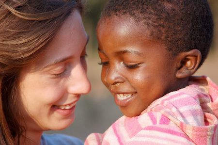 """March 28, 2016-Center """"Smile to Africa"""" in the Village Pomerini in Tanzania-Africa-An unidentified volunteer doctor embraces an unidentified African child, a little patients sick of AIDS, in a gesture of affection that expresses happiness for the success Editorial"""