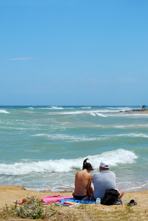 swept: A couple of tourists on the beach swept by the Mistral in Apulia - Italy Stock Photo