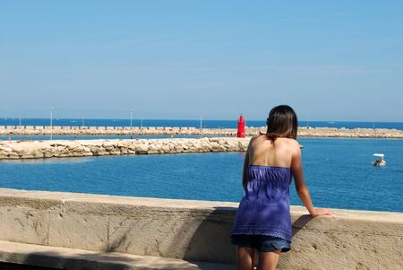 A woman while contemplating the sea of Trani deep in thought