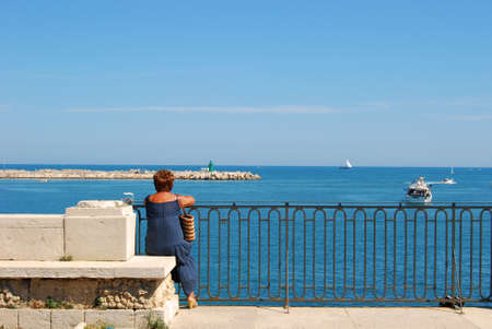 breakwaters: Marini thoughts - A woman while contemplating the sea of Trani deep in thought Stock Photo