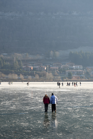 Sunday, January 8, 2017-Lake Endine-Bergamo-Lombardia-Italy-A crowd of unidentified people enjoy walking on the rare phenomenon of glaciation of Lake Endine just 373 m.s.l. Stock Photo
