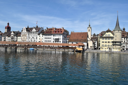 March 30, 2017-Lucerne-Switzerland-panoramic view of the city of Lucerne and its lake, popular with tourists who flock to its shores. In the foreground the famous covered bridge built in wood