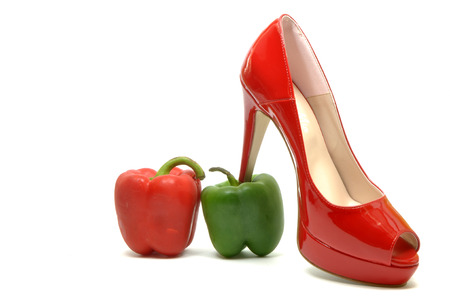 Sexy female shoes between a red and a green pepper
