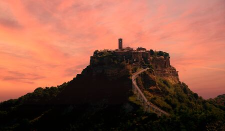 A suggestive view of the town of Civita Bagnoregio at sunset perched on a crumbling rock spur Stock fotó