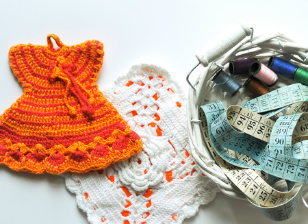 needlecraft: hand knit pot holders next to scissors, tape measure and colored spools Stock Photo