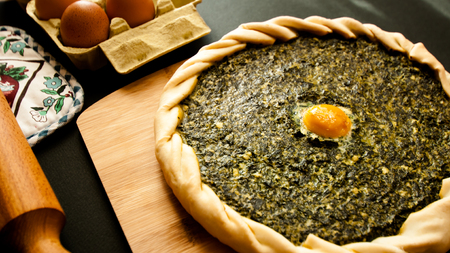 spinach savory pie displayed with some ingredients