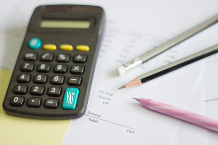 examiner: a calculator is on a balance sheet numbers are statistics. photo icon for sales, profit and cost.