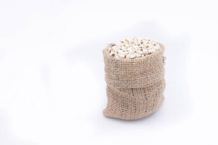 gunny bag: jobs tears in gunny bag, chinese pearl barley , on white background Stock Photo
