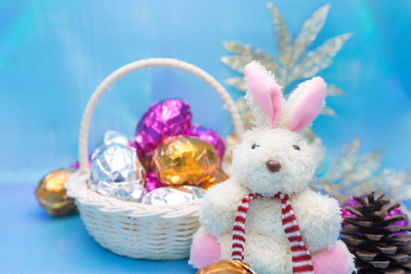 cowering: Cute little easter bunny with colored eggs on shining blue background Stock Photo