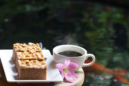 custard slice: Toffee cake , hot black coffee and pink flowers on a wooden table . The idea of refreshing in the morning.