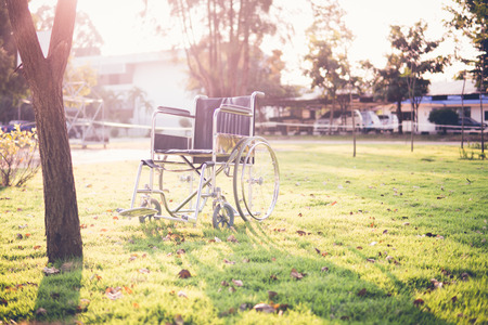Empty wheelchair on the garden at sunset. Miracle concept. Healed person raised and went away or hope to heal