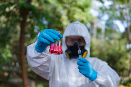 doctor or scientist in laboratory holding a syringe on grren natural bacground,selective focus
