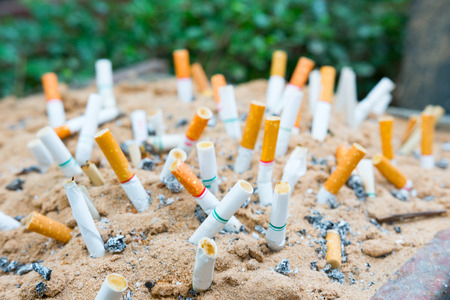 The rest of cigarettes in the ashtray. There are many types of cigarette stub on the sand in the ashtray. A cigarette is not good for health. It is not allow to smoking in the public area in Thailand. 版權商用圖片