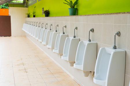 Close up row of outdoor urinals men public toilet, design of white ceramic urinals for men in toilet room.