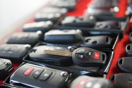 Slotenmakertribune met verscheidenheid van auto en van keys op afstand op rode achtergrond
