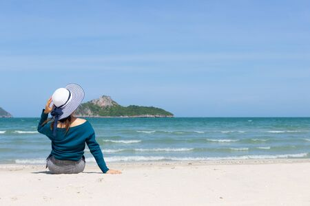 Woman wear summer dress and straw hats sitting on the beach look at sea sky mountain .Time to relax in summer lifestyle outdoor on tropical island beach.concept for Summer time  vacation on the beach. Stock Photo