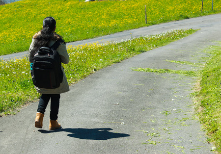 Female traveller with backpack walking along trail of road with green grass on both sides. The roads are joining and will reach cross roads. Stock Photo
