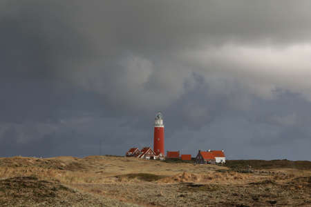 The red lighthouse and houses on Texel island, Holland Stock Photo