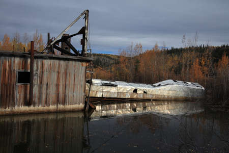 The remains of delelict mining dredge outside of Dawson City, Stock Photo