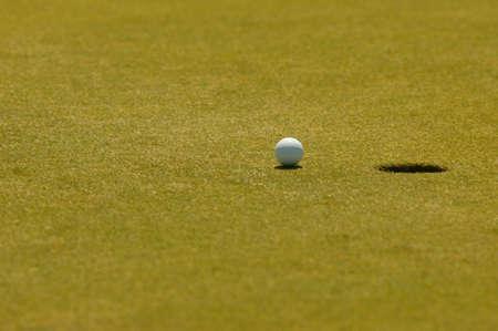 Ein Golfball auf dem Wegg in das Hole, beim putten