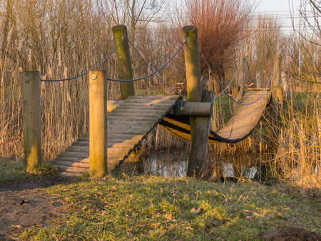A small wooden footbridge over a stream by a cold winter sunset photo
