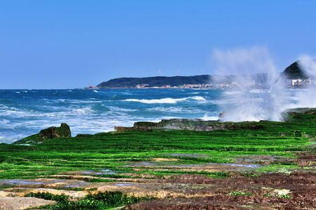 city scape: Laomei Green Reef is a beach located at north coast of Taiwan, now it become famous because of its incredible wave-cut volcanic lava covered with green seaweeds   New Taipei City, Taiwan Stock Photo