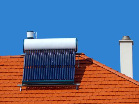 hot summer: Las c�lulas solares para la energ�a ecol�gica, calentador de agua de energ�a solar y la chimenea Foto de archivo