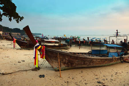 Longboats at sunset on Phi Phi island, Thailand photo
