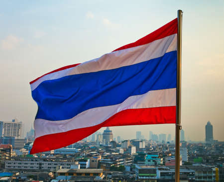 Thailand flag waving in the wind with Bangkok in background photo