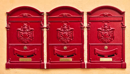 Three red maiboxes in the city of Cortona, Umbria, Italy photo