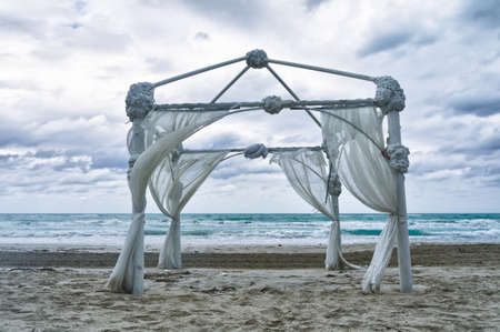 Wedding archway arranged on the sand in preparation for a beach wedding ceremony photo