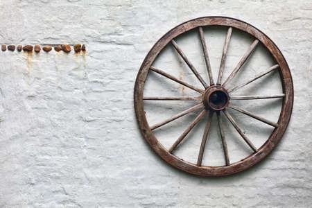 Rustic wagon wheel hanging on a wall Фото со стока