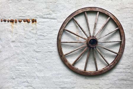 Rustic wagon wheel hanging on a wall Standard-Bild