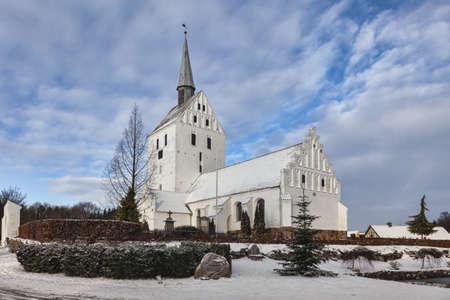 White medieval church in Svindinge, Denmark on a sunny day photo