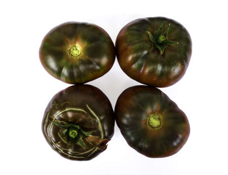 Fresh black beef tomatoes presented on a white background