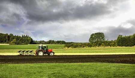 Kleinschalige landbouw met trekker en ploeg op gebied Stockfoto