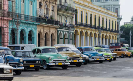 Street scene with vintage car and worn out buildings in Havana, Cuba.